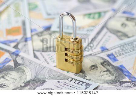 Yellow closed padlock and dollars (DOF shallow)