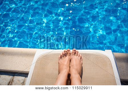 Female Legs On A Sun Lounger On The Background Of The Pool