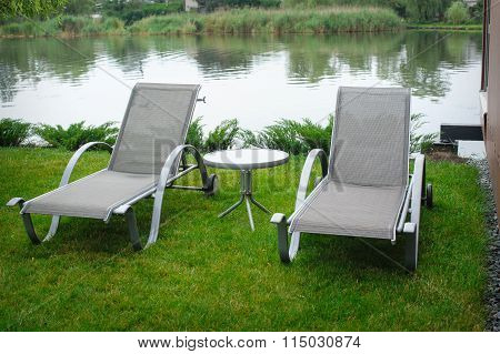 Two Deck Chairs On The Bank Of The River