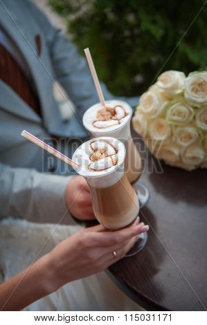 Hands Of Bride And Groom. Cappuccino Or Latte Coffee With Heart Shape. Bride And Groom Drink A Cup O
