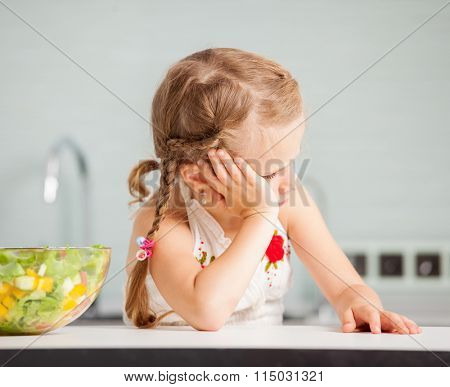 Little girl refuses to eat salad. Child looks with disgust for food