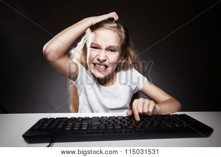 Child looks with disappointment to computer. Computer addiction