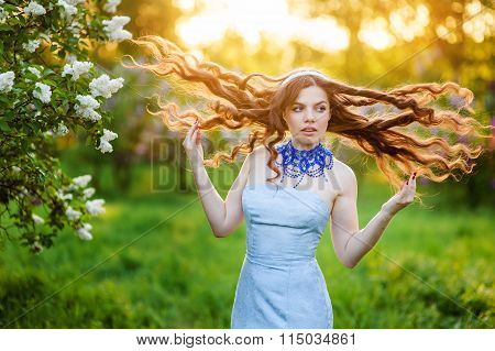 Happy Young Woman In A Park In Spring Lilac With Loosened Hair
