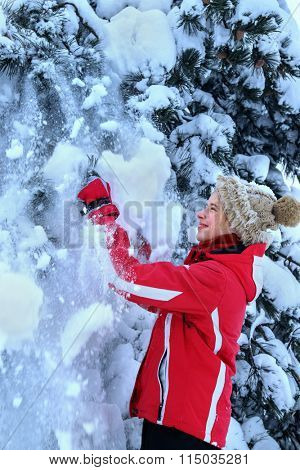 Girl in winter clothes and hat joy falling snow near tree.