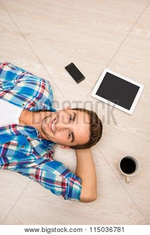 Top View Photo Of Smiling Man Lying On The Floor With Phone, Tablet And Cup Of Coffee