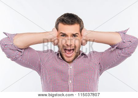 Young Man Covering His Ears And Shouting