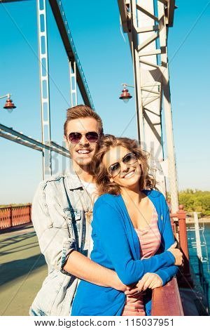 Cheerful Couple Embracing Each Other On The Bridge