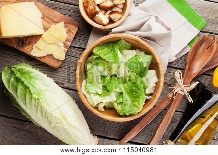 Fresh healthy caesar salad cooking on wooden table. Top view