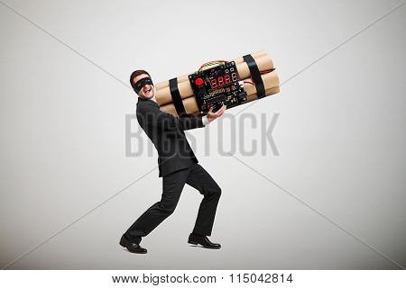 laughing offender in black mask carrying big bomb and looking at camera over light grey background