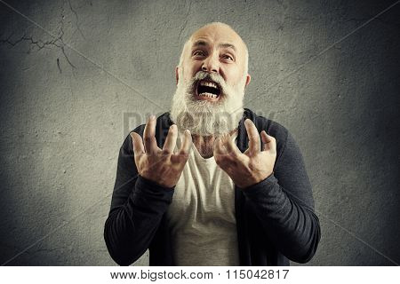 portrait of yelling senior man over grey background
