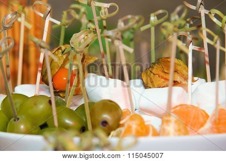 Fruit on skewers. Grapes and oranges on the table.