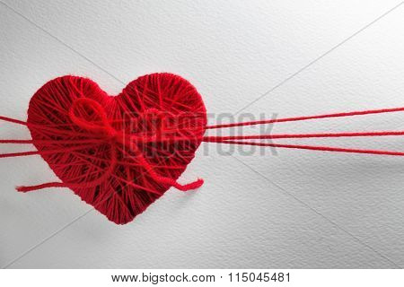 Red heart made from wool on textured white background
