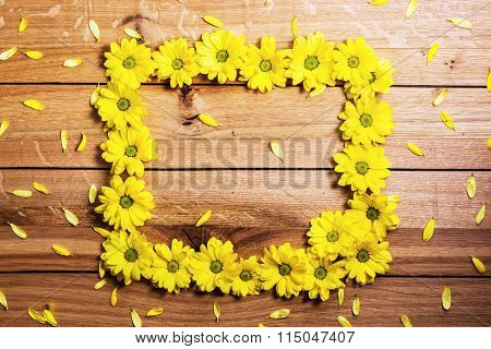 Fresh spring flowers and petals making frame on rustic wood. Place for text on Valentine's Day, Mother's Day etc. Daisy flower