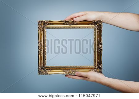 Man holding an antique style golden frame in his hands.