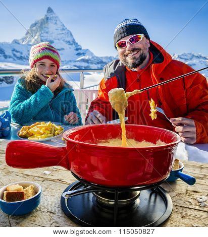 Ski lunch in a restaurant, Fondue, traditional Swiss dish - Matterhorn in Swiss Alps in background