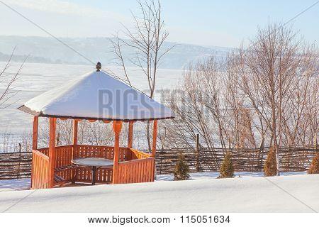 wooden gazebo in the snow