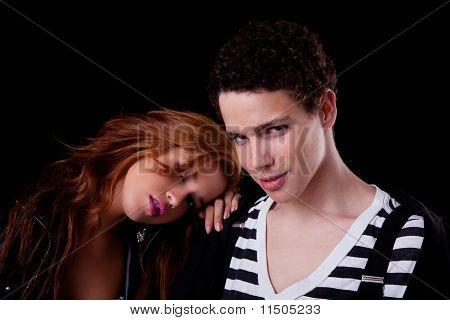 Gut aussehend, junges Paar, sie mit dem Kopf auf der Schulter, isoliert auf schwarz, Studio Shot