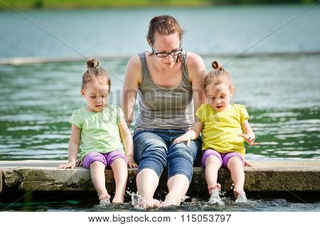 Mother And Little Children Twin Girls Are Playing On A Lake