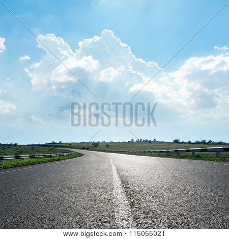 black asphalt road with white line under clouds in blue sky