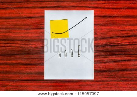 Curve Graph Printed On A Sheet Of Paper And Yellow Note With Arranged By Size Paper Clips