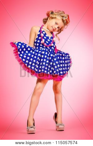 Pretty little girl in her mother's shoes and hair curlers. Kid's fashion, cosmetics. Pin-up style.