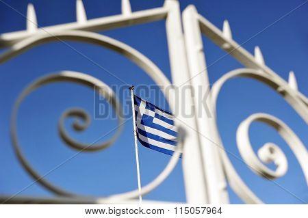 Greek flag is waving on the wind behind openwork metal fence