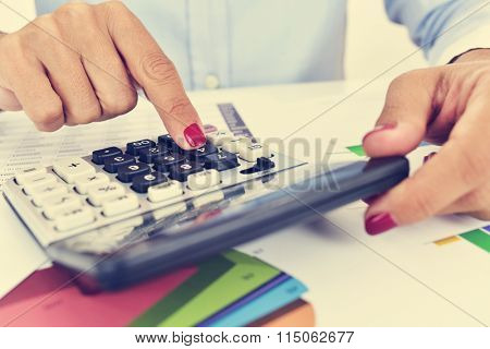 a businesswoman using an electronic calculator in her office, with a desk full of charts