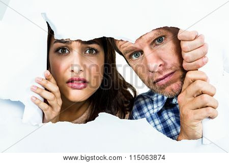 Portrait of fearful couple peeking through torn paper