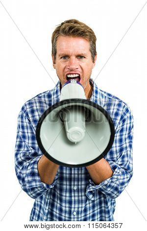 Portrait of angry man shouting through megaphone while standing against white background