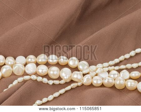 Beads Of Pearl On The Brown Fabric