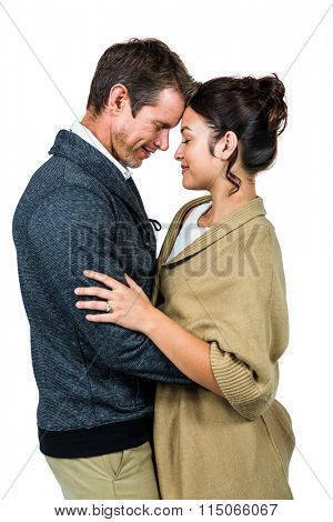 Side view of affectionate couple hugging against white background