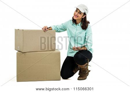 Portrait of delivery woman with clipboard kneeling by box against white background