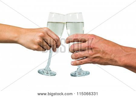 Cropped hand of couple holding champagne flute against white background