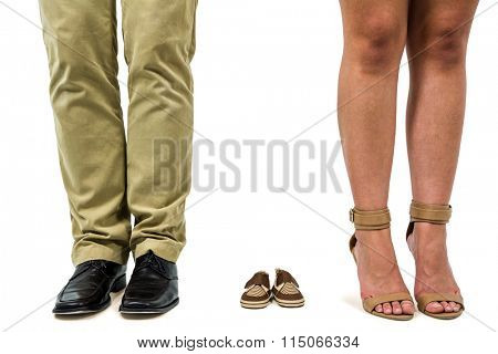 Low section of couple amidst baby booties over white background