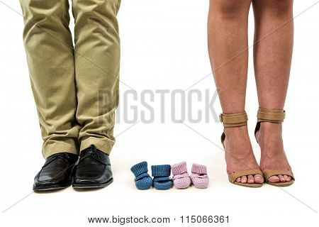 Close-up of man and woman amidst baby booties against white background