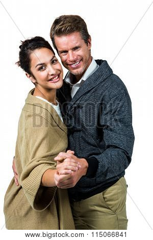 Portrait of happy affectionate couple dancing against white background