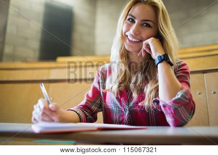 Smiling student posing for camera in lecture hall