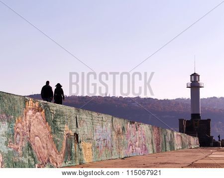 Varna - 18 November: People Walk Near The Lighthouse At The Seaport Of Varna, Graffiti On A Concrete