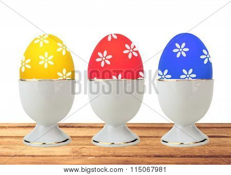 Colorful Easter Eggs In Stand On Table Isolated On White