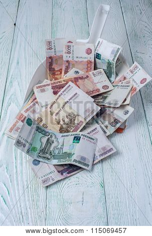 Rubles in garbage scoop on wooden background