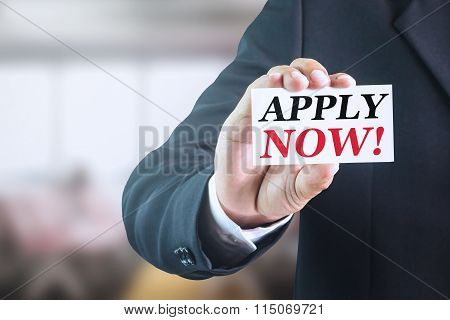 Businessman holding a white sign with the message apply now!.