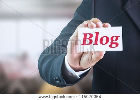 Businessman holding a white sign with the message Blog.