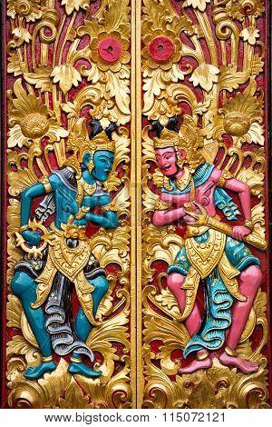 carved detail of guard mythological god on Balinese temple door