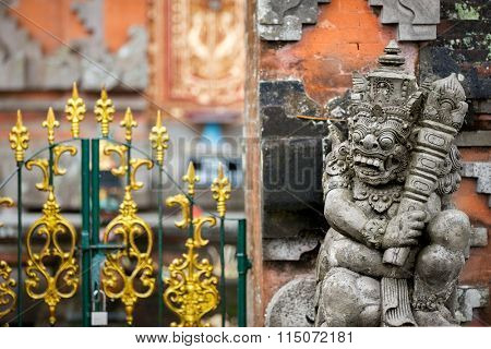 Traditional guard demon statue carved in dark stone in front of the gate of Hindu temple in tropical Bali