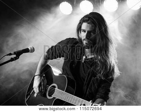 Singing And Playing Acoustic Guitar On Stage