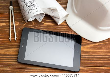 Workplace of architect - Architectural project, plan, blueprint rolls and tablet pc, pen, safety hel