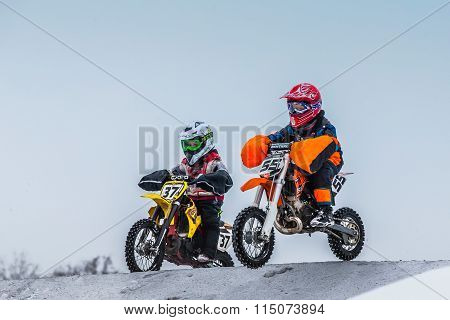 two young boy racers on motorcycle ride through hill of motocross