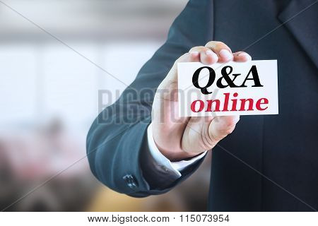 Businessman holding a white sign with the message Q&A online.