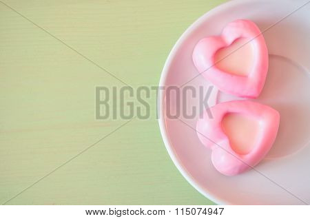Heart-shaped Light Pink Souffle Cakes On The Green Wooden Table. Selective Soft Focus On The Cake An