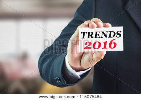 Businessman holding a white sign with the message trends2016.